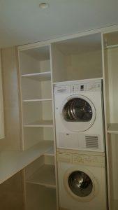 Zona de serveis de disseny al costat de la cuina amb instal·lació de rentadora i secadora.