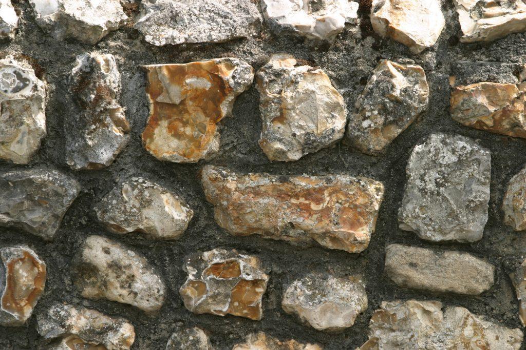 """Som especialistes en construcció de murs de pedra de tot tipus. Pedra calcària blanca i forta, de gran mida que ens servirà per a fer d'entrada un marge esglaonat en diverses feixes. Ens han portat una pedra força gran però alhora de bon trencar, tot i que bastant dura, un bon calcari. Com que és un primer projecte en aquests terrenys, es va acordar que aquest marge esglaonat de pedra seca a la part del darrera de la casa, el faríem amb les pedres més grans en la primera feixa arran de terra i amb la tècnica de construcció poc adobada, tocant just el necessari les pedres per encaixar-les bé... Tanmateix, en els murs superiors que fan prop d'un metre la tècnica utilitzada és força similar a la tècnica en murs mallorquins, on les pedres encaixen malgrat les formes diverses que tenen i no precisament planes... Aquí les pedres han necessitat ser treballades amb el punxó i el """"topu"""", per a fer un mur, com es diu en el vocabulari dels margers, una mica adobat."""
